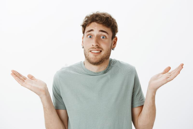 Close-up shot of questioned awkward handsome male in earrings, shrugging and spreading palms cluelessly, being unaware. And knowing nothing what to do, standing stock photo