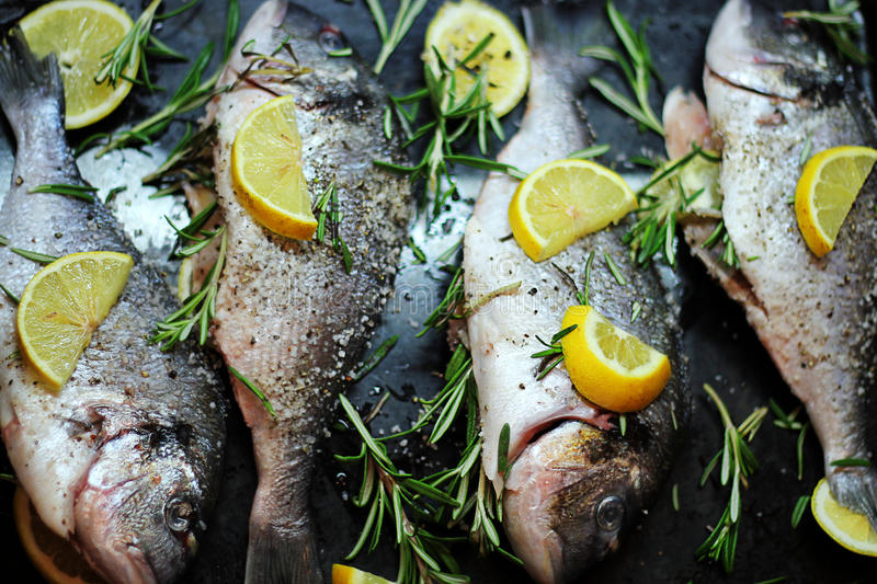 Close-up shot of raw fish with lemon ready for cooking. Sparus aurata. Concept of healthy food. Recipe of gilt-head bream fish stock photo
