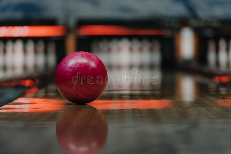 Close-up shot of red bowling ball lying on alley under. Warm light royalty free stock image