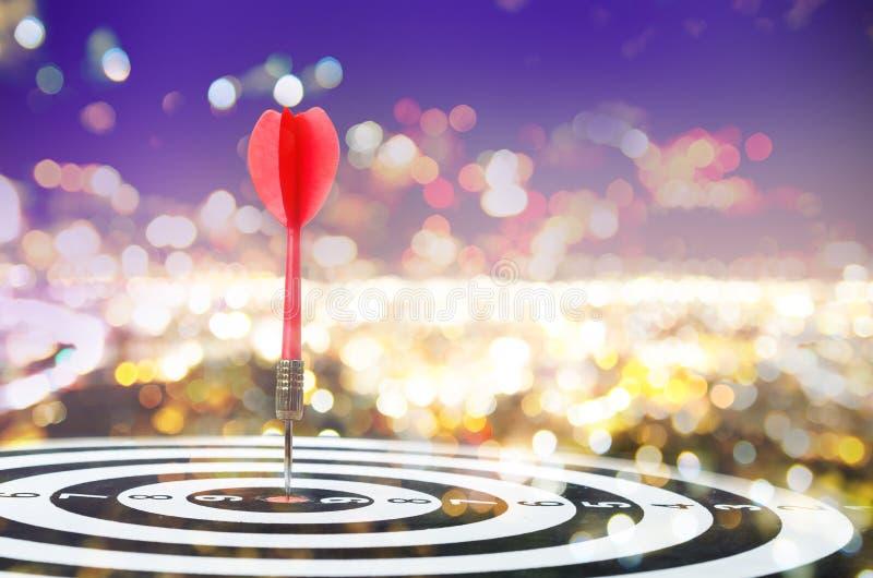 Close up shot red dart arrow on center of dartboard on bokeh blu royalty free stock photography