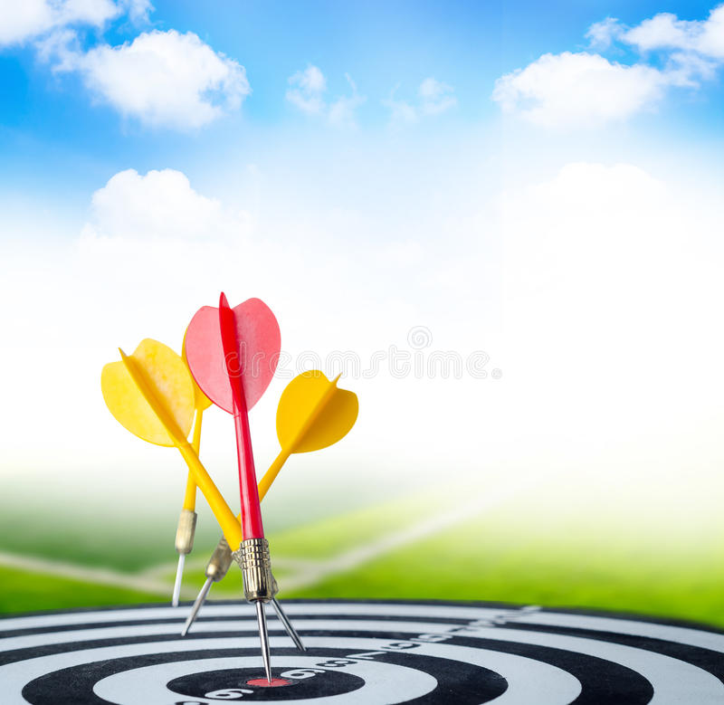 Close up shot red dart arrow on center of dartboard and yellow a. Rrow not hit the target with copyspace, metaphor to target success, with green field and royalty free stock photography