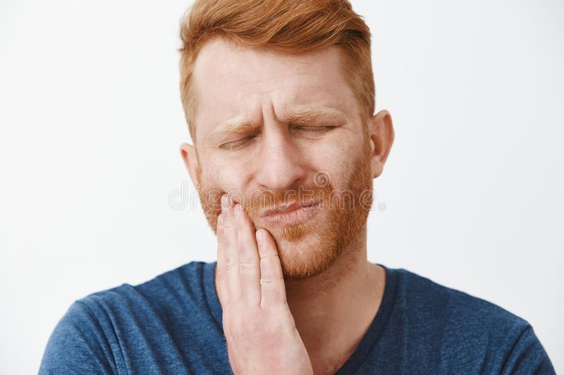 Close-up shot of redhead man with beard feeling pain in teeth, frowning and making suffering expression with closed eyes royalty free stock images