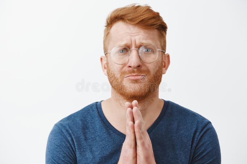 Close-up shot of redhead man in need standing with hands in pray over chest, pursing lips and frowning while asking stock image