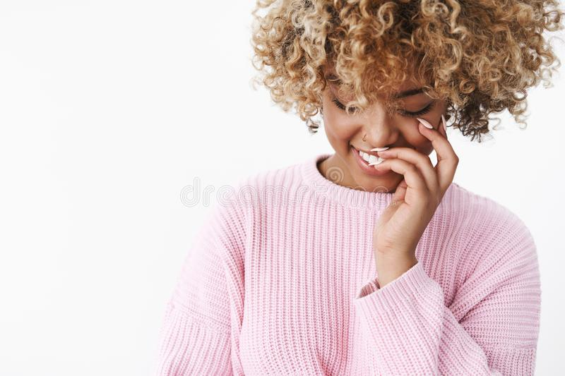 Close-up shot of romantic and cute tender african american woman in stylish comfy warm sweater looking down shy and. Romantic smiling and giggling cheeky royalty free stock images