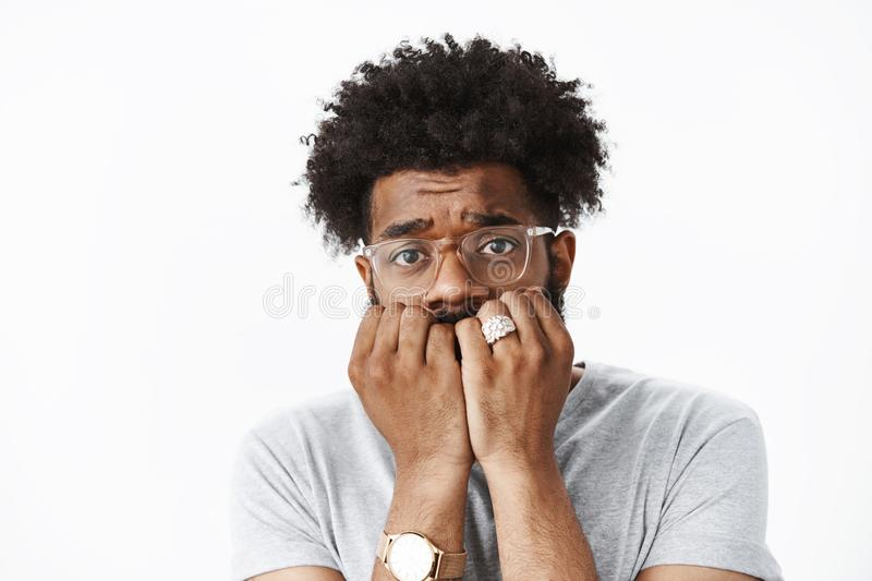 Close-up shot of scared and insecure young african american man with afro hairstyle in watch and glasses biting. Fingernails raising eyebrows silly and timid royalty free stock photography