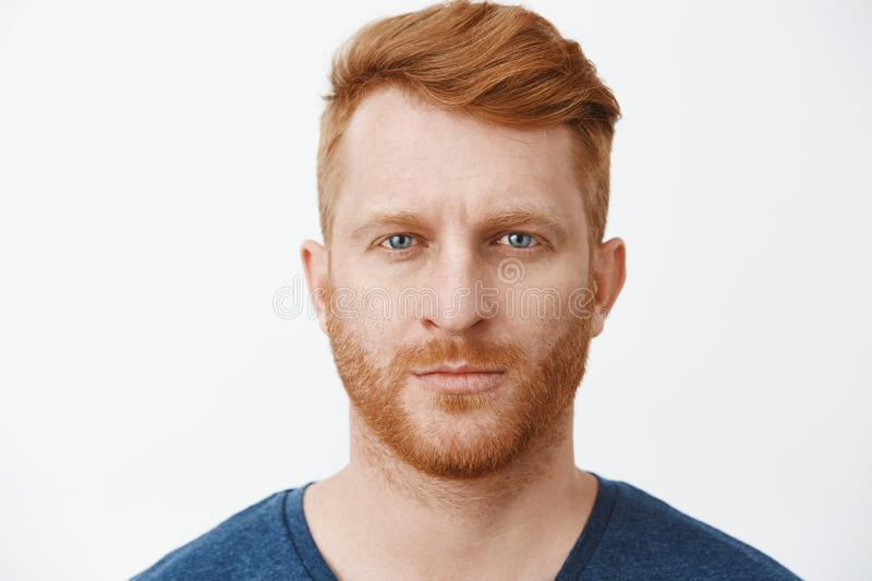 Close-up shot of serious-looking handsome adult european man with red hair and beard staring at camera with focused and stock images