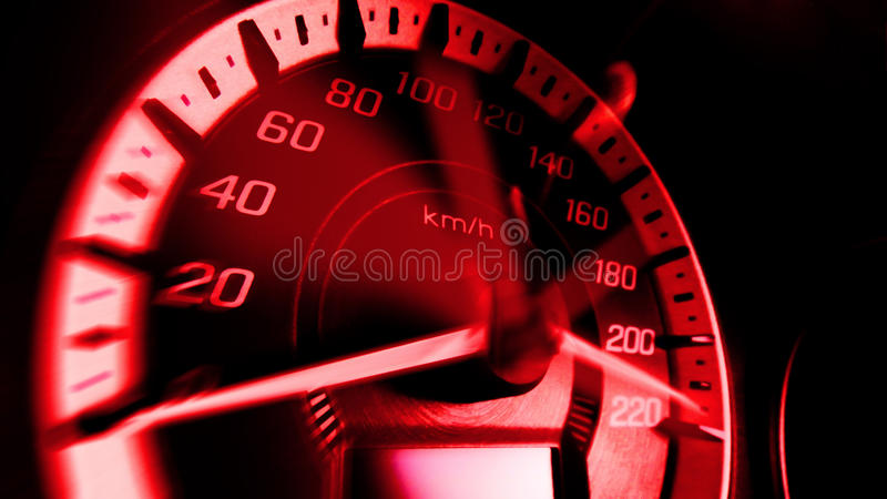 Close up shot of a speed meter in a car with red light speed at 220 Km/H in concept racing car.  stock photo