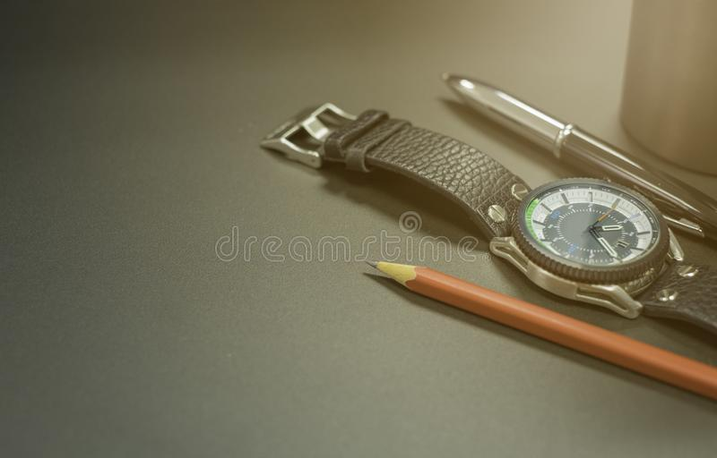 Close up shot of Stainless steel watch case, leather strap with pen and red pencil On black metal surface. Background royalty free stock photos