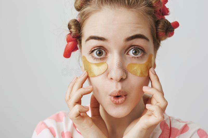 Close-up shot of surprised girl in hair-curlers and pajamas, applying eye patch mask, touching it with hands, folding royalty free stock photo