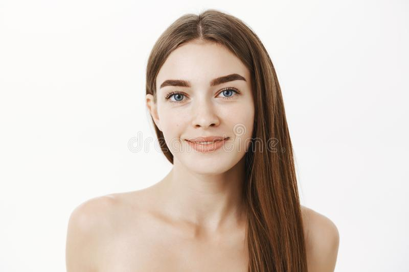 Close-up shot of tender and feminine cute young woman with long brown hair standing naked over grey wall and smiling stock photo