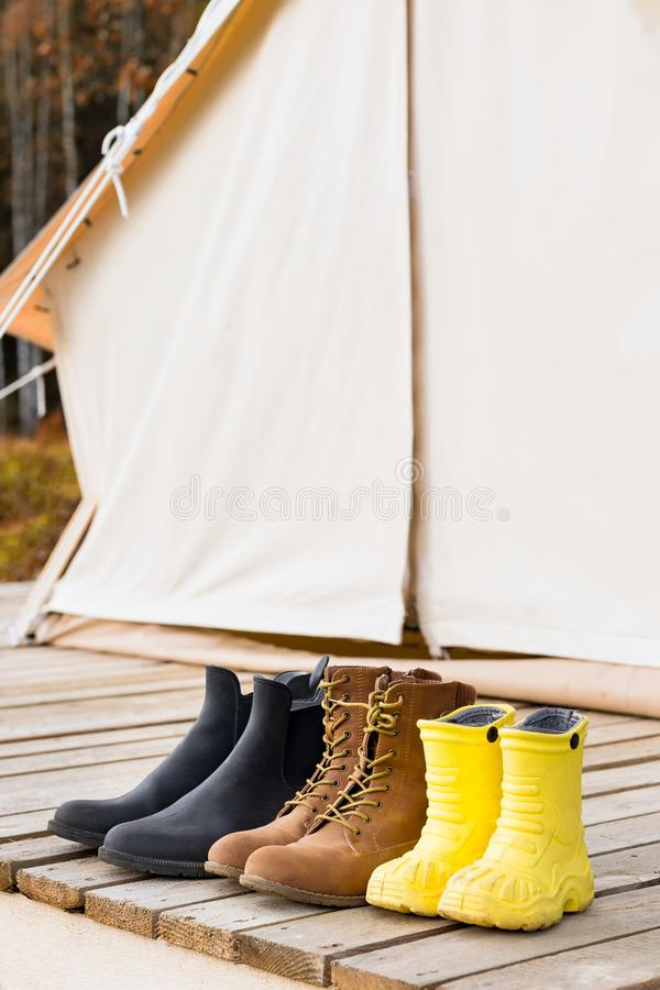 Close-up shot of three different pair of shoes near a canvas tent stock photos