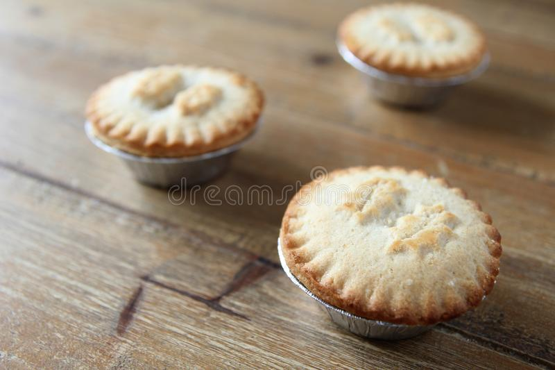 Close up shot of three mince pies in foil cases, traditional Christmas dessert royalty free stock photos