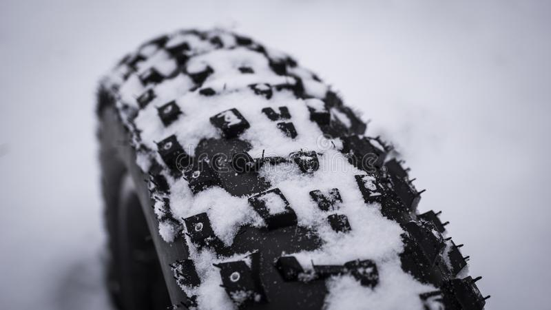 Close up shot of the tread on a fat mountain bike tire in snow . royalty free stock image