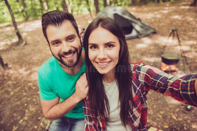 Close up shot of two young cheerful lovers in the summer nice wood, embracing, posing for a selfie shot, that beautiful brunette royalty free stock photography
