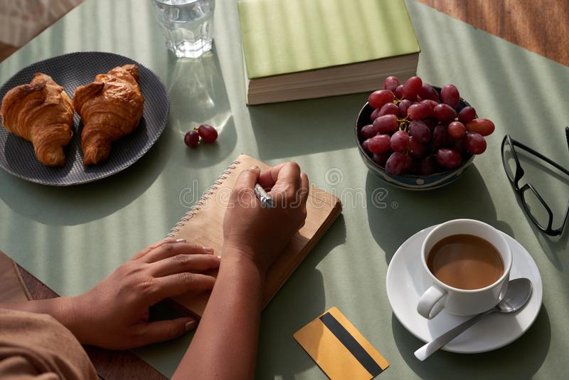 Taking Notes at Kitchen Table. Close-up shot of unrecognizable woman taking necessary notes while enjoying appetizing breakfast at home stock photography