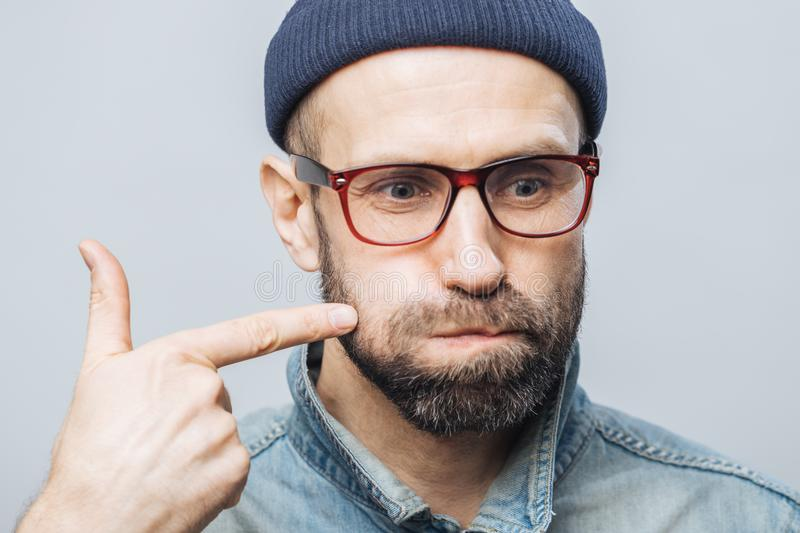 Close up shot of unshaven male with thick beard and mustache blows cheeks and indicates with fore finger, being concentrated on so royalty free stock images