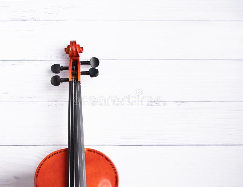 Close-up shot violin orchestra instrumental over white wooden background with copy space royalty free stock photography