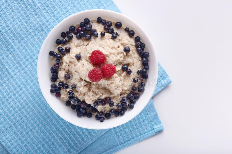 Close up shot of white bowl with porridge being on blue kitchen towel, oatmeal decorated with raspberry and blueberry at top, stock image