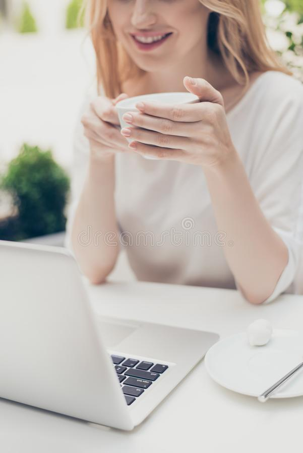Close up shot of woman holding mug of tea sitting in the cafeteria watching film having break royalty free stock photos
