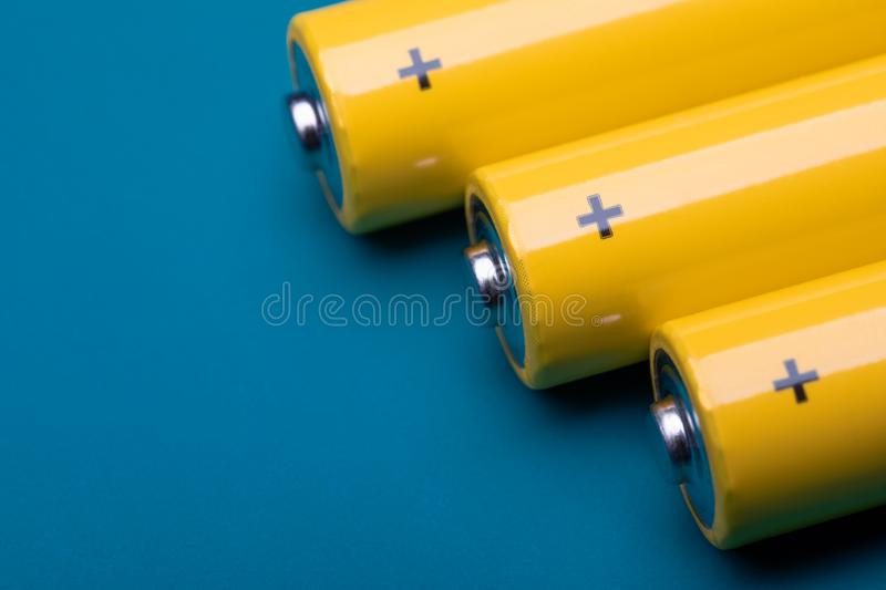 Yellow alkaline batteries on blue background. Close up shot of yellow AA alkaline or rechargeable NiMH batteries on blue background, shallow focus royalty free stock photo