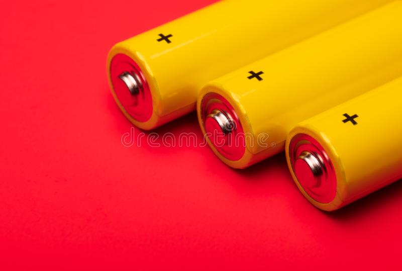 Yellow alkaline batteries on red background. Close up shot of yellow AA alkaline or rechargeable NiMH batteries on red background, shallow focus royalty free stock images