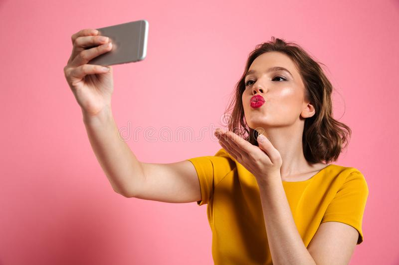 Close-up shot of young attractive woman with bright makeup sending air kiss while taking selfie on mobile phone. Isolated over pink background stock photos