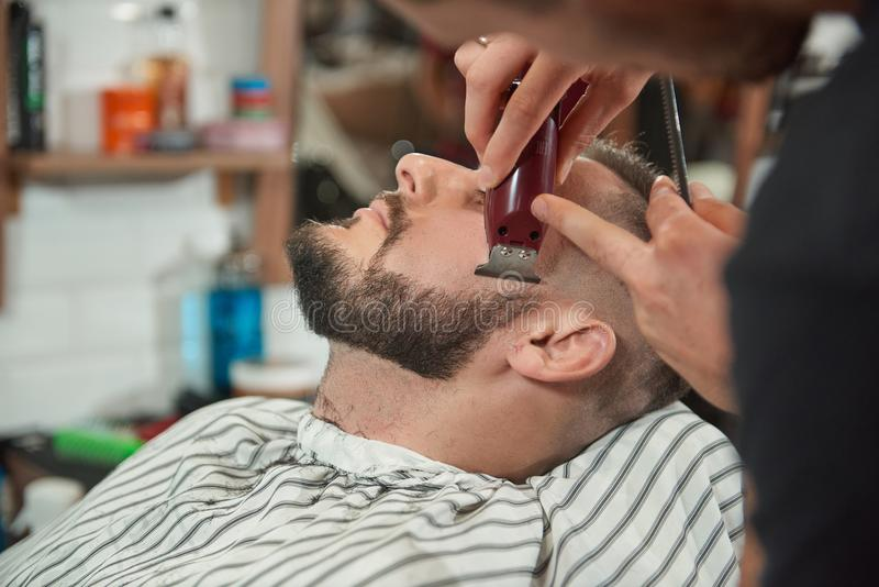 Young man at the barbershop. Close up shot of a young bearded men getting his beard shaped and trimmed at the barbershop royalty free stock images