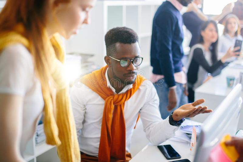 Close up shot of young black man showing computer to ginger woman royalty free stock images