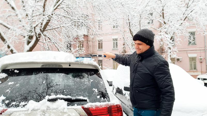 Close up shot of young handsome man in black coat and hat trying to clean up snow covered car after blizzard with brush royalty free stock photography