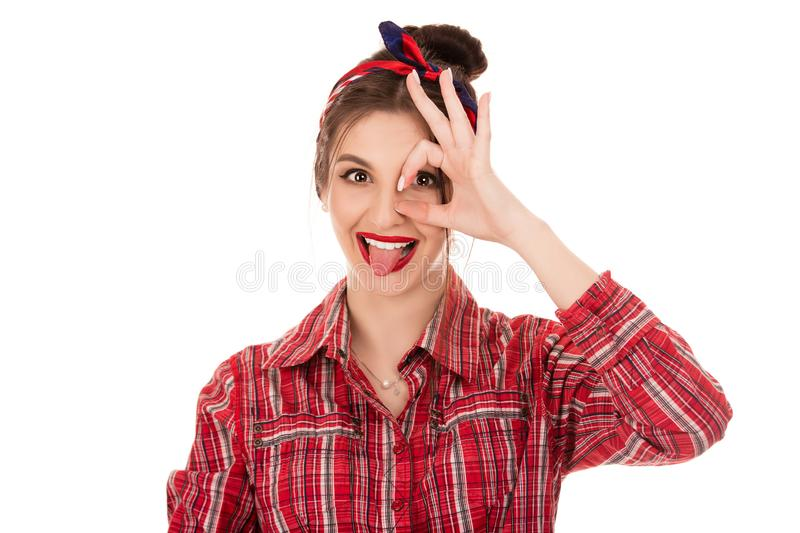 Positive woman looking at camera through hand in ok gesture. Close up shot of young positive woman with long dark hair looking at camera through hand in ok stock photo