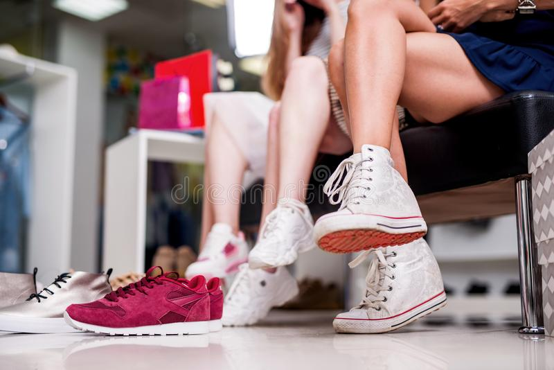 Close-up shot of young women trying on different footwear while sitting in a shoe store.  royalty free stock photography