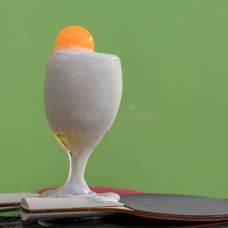 Bubbles of beer in a glass with a ping pong ball. Close-up shots of beer bubbles in a glass with orange ping-pong floats, which have green walls as backgrounds royalty free stock photo