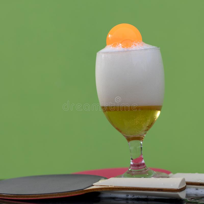 Bubbles of beer in a glass with a ping pong ball. Close-up shots of beer bubbles in a glass with orange ping-pong floats, which have green walls as backgrounds stock photo
