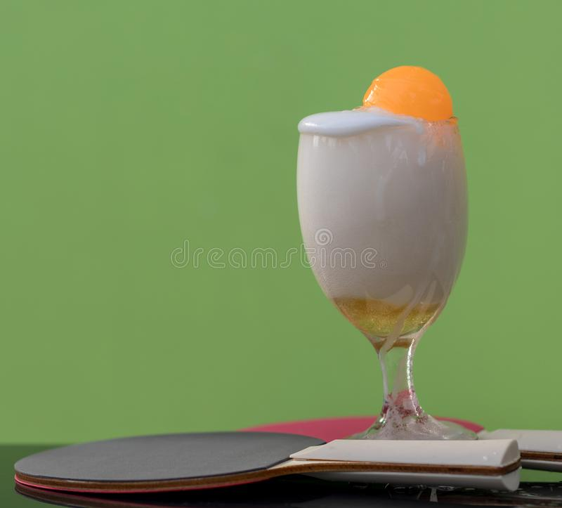 Bubbles of beer in a glass with a ping pong ball. Close-up shots of beer bubbles in a glass with orange ping-pong floats, which have green walls as backgrounds stock photos