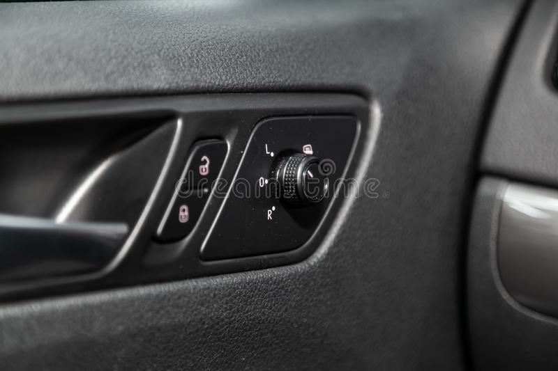 Modern car interior: parts, buttons, knobs. Close-up of the side door buttons:  mirror, adjustment buttons, door lock. modern car interior: parts, buttons, knobs royalty free stock photography