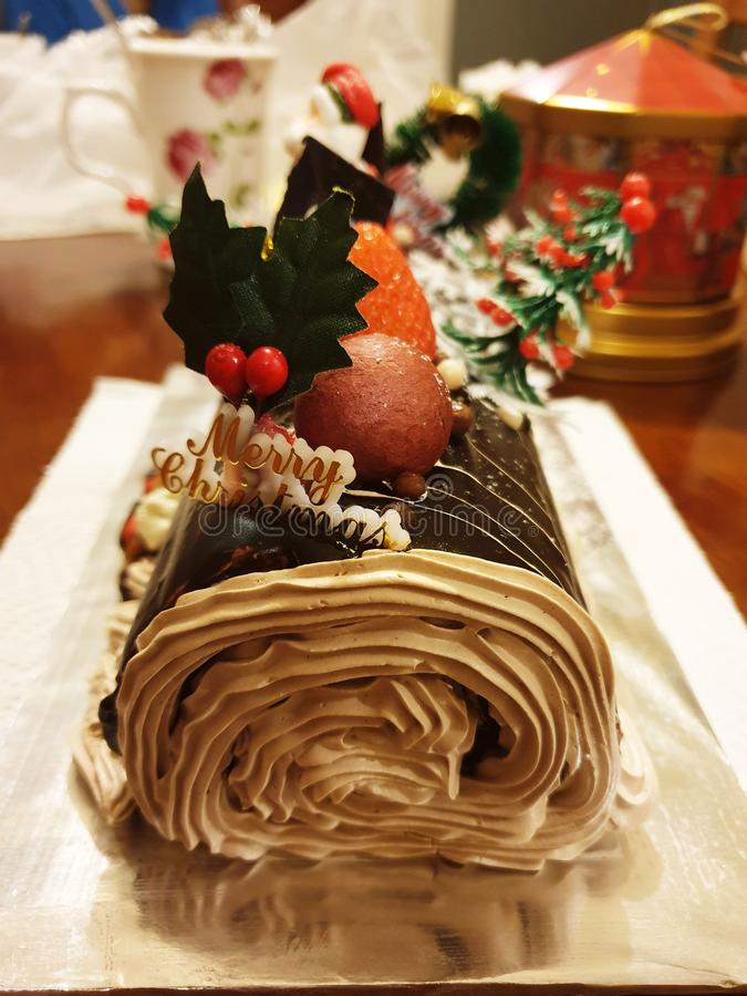 Close-up side image of brown creamy Yule Log dessert Christmas cake with decoration in foreground on table royalty free stock images