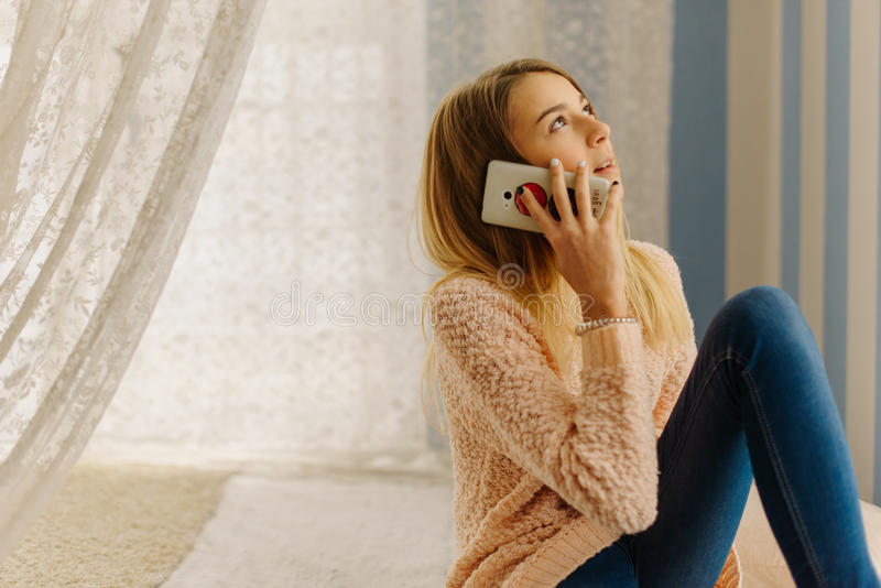 The close-up side portrait of the young blond teenager talking on the mobile phone while sitting on the bed. stock images