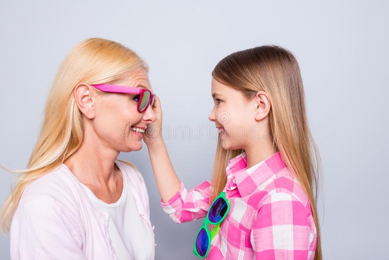 Close up side profile photo funky two people blond hair she her granny little granddaughter ready holiday celebrate look. Eyes wear specs pink plaid checkered royalty free stock images