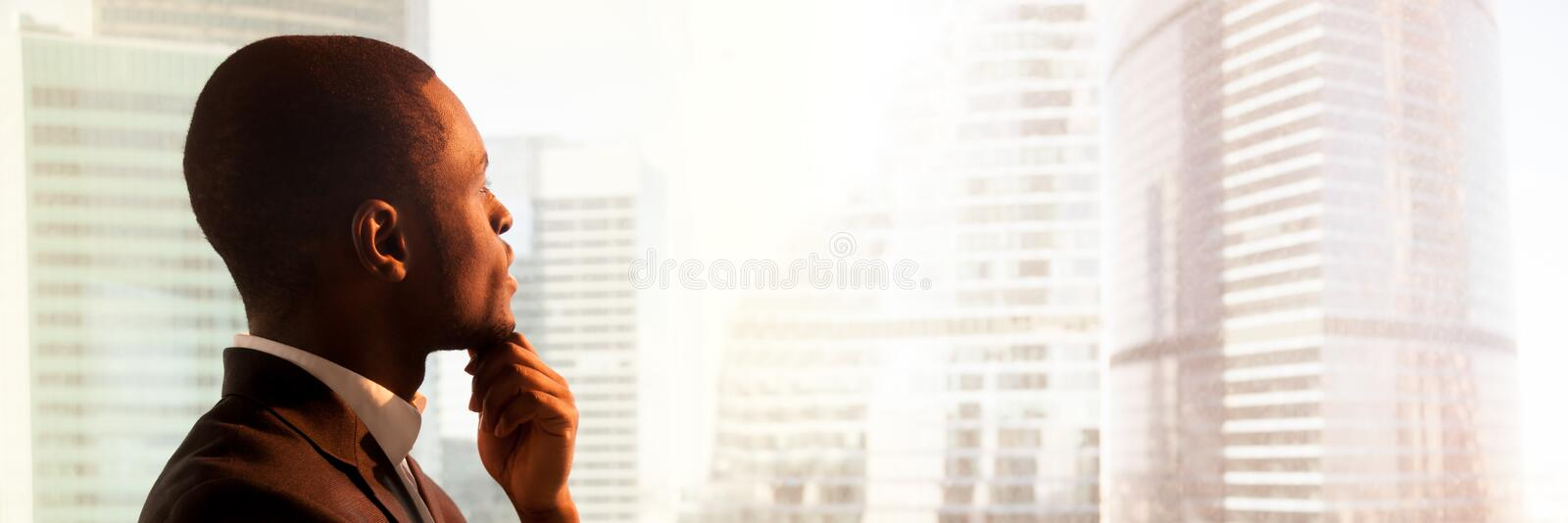 Close up side view black businessman standing near window thinking royalty free stock image