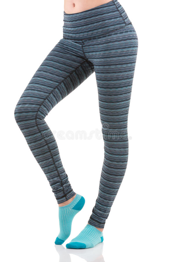 Close up side view of fit woman legs warming up in colorful striped sports leggings wearing blue socks royalty free stock image