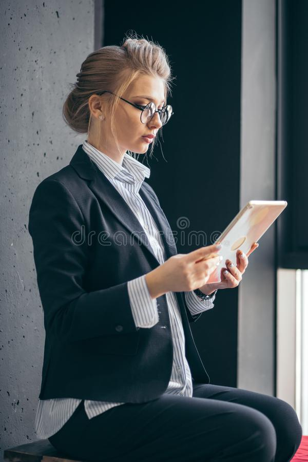 Close up side view portrait of elegant female watching video lessons stock image