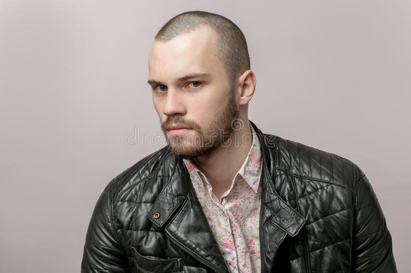 Close up side view portrait of a serious , brutal guy in black leather jacket stock images