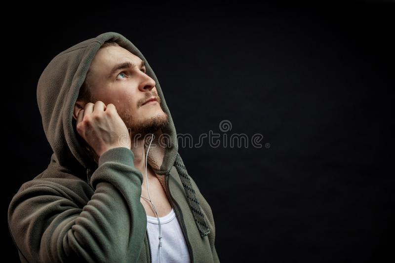 Close up side view portrait of sporty guy in geen hoodie looking up. Music and sport concept. copyspace royalty free stock images