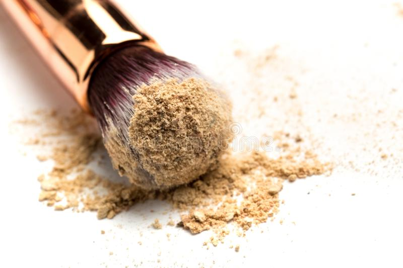 Close-up side view of professional make-up brush with natural bristle and black ferrule with crashed eyeshadow isolated on white royalty free stock photos