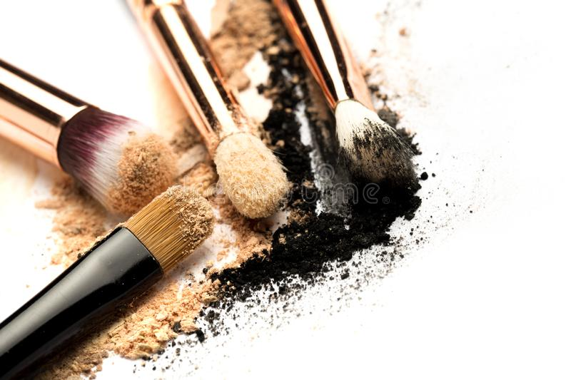 Close-up side view of professional make-up brush with natural bristle and black ferrule with crashed eyeshadow isolated on white stock images