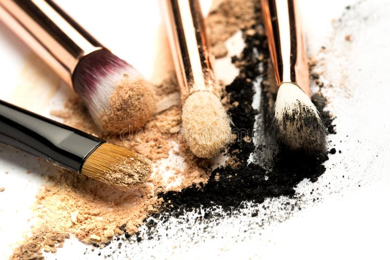 Close-up side view of professional make-up brush with natural bristle and black ferrule with crashed eyeshadow isolated on white royalty free stock images