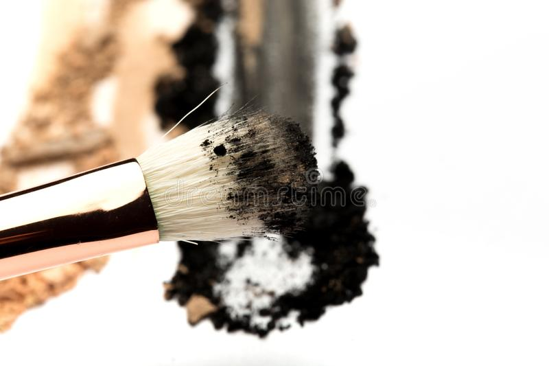 Close-up side view of professional make-up brush with natural bristle and black ferrule with crashed eyeshadow isolated on white royalty free stock photo