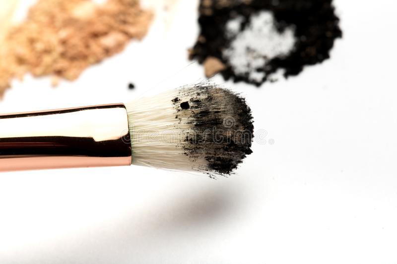 Close-up side view of professional make-up brush with natural bristle and black ferrule with crashed eyeshadow isolated on white royalty free stock photography