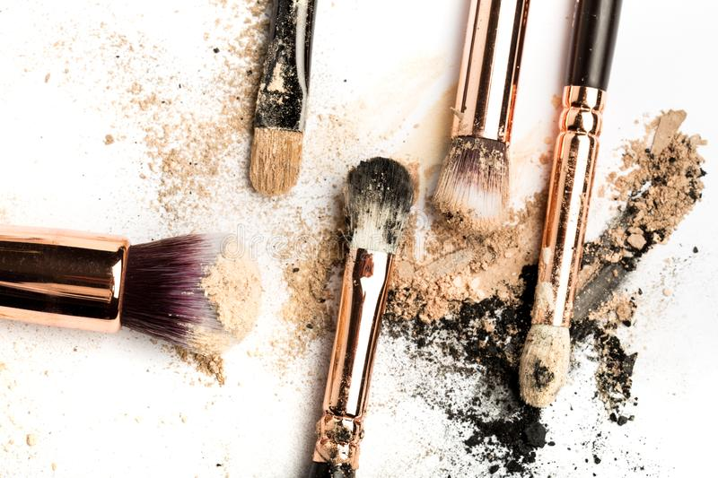 Close-up side view of professional make-up brush with natural bristle and black ferrule with crashed eyeshadow isolated on white stock photography