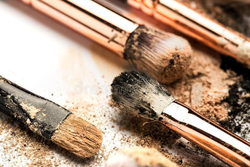 Close-up side view of professional make-up brush with natural bristle and black ferrule with crashed eyeshadow isolated on white stock photo